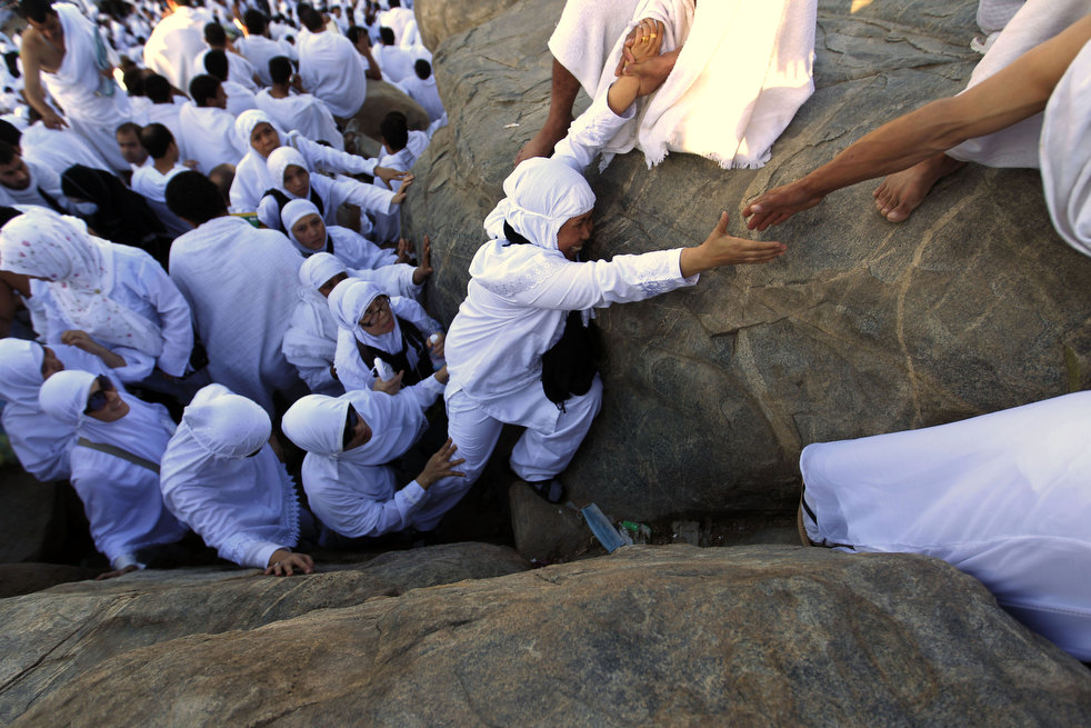 Muslim pilgrims climb a rocky hill called the Mountain of Mercy, on the Plain of Arafat near Mecca, Saudi Arabia, Saturday, Nov. 5, 2011. The annual Islamic pilgrimage draws 2.5 million visitors each year, making it the largest yearly gathering of people in the world. (AP Photo/Hassan Ammar)