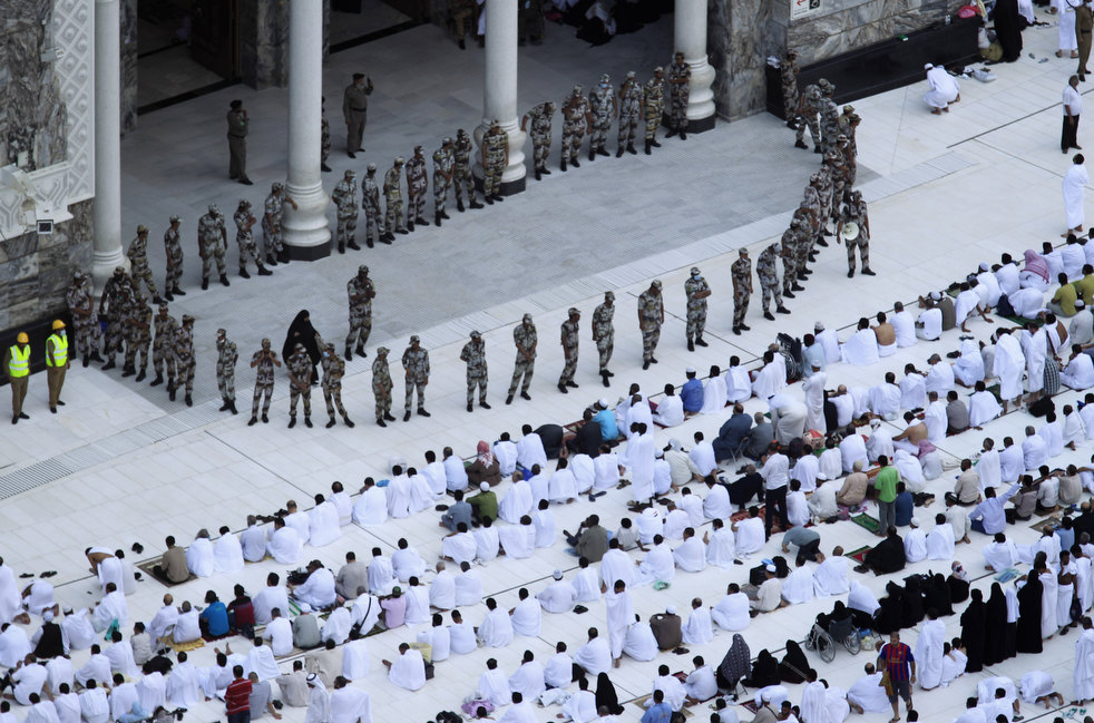 Saudi special forces stand guard as Muslim pilgrims pray during Friday prayers at the Grand Mosque, in Mecca, Saudi Arabia, Friday, Nov. 4, 2011. The annual Islamic pilgrimage draws three million visitors each year, making it the largest yearly gathering of people in the world. The Hajj will begin on November 5. (AP Photo/Hassan Ammar)
