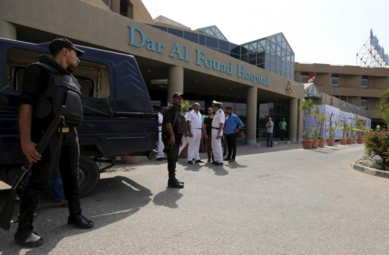 Egyptian police personnel stand guard outside Dar Al Fouad Hospital, where injured tourists are recovering, in Cairo