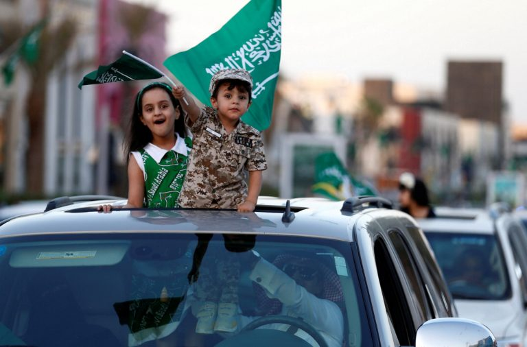 Saudi children riding in a car celebrate Saudi National Day on a street in Riyadh